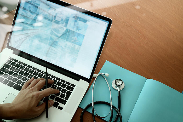 top view of Medicine doctor hand working with modern computer and smart phone on wooden desk as medical concept - ARTES ISAAC